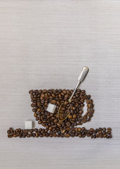 Coffee beans in a cup, spoon and sugar