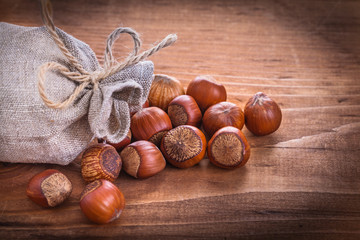 hazelnuts sack on vintage wooden board food and drink concep