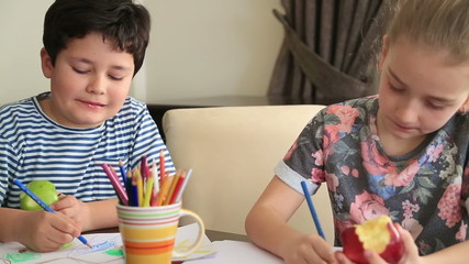 Little girl and boy drawing at home