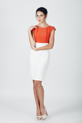 Fashion photo of young magnificent woman in a white and orange d
