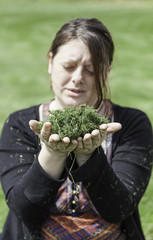 Young woman blowing grass