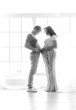 pregnant wife and husband standing and touching by stomachs