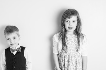 black and white portrait of brother and sister against a wall
