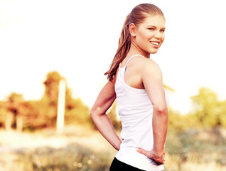 Fitess model on the nature. Young female runner exercising