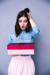 Surprised woman holding gift
