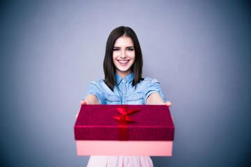 Smiling woman giving a gift box at camera