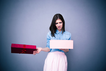 Dissatisfied woman opening gift