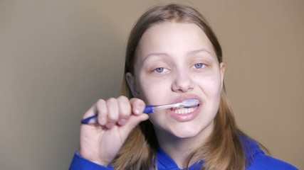 Unhappy teen girl brushing teeth