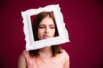 Pensive young woman with frame on head