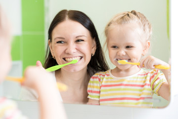 Hygiene. Happy mother and child brushing teeth together
