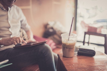 Ice coffee in plastic glass with wallet in cafe with businessman © nuiiko