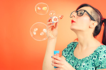Pretty lady blowing colorful bubbles