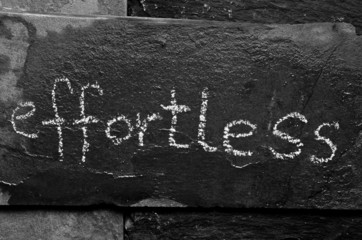 The word EFFORTLESS written with chalk on black stone.