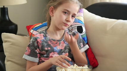 Little girl zapping and eating popcorn