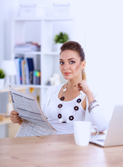 Cute businesswoman holding newspaper sitting at her desk in