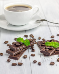 Dark chocolate decorated with coffee beans and cup of coffee