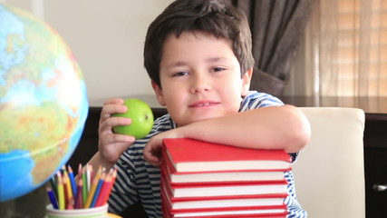 Young schoolboy looking at camera and eating apple