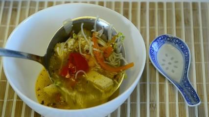 Asiatische Suppe mit Tofu, servieren