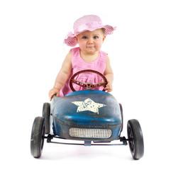 kleines Mädchen mit Hut im Tretauto