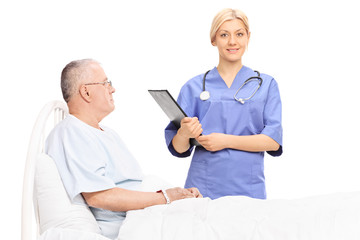 Female doctor standing next to a mature patient