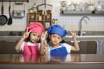 Two little chef show victory sign