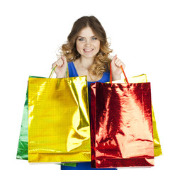 Happy young blonde girl with colorful shopping bags in blue sexy
