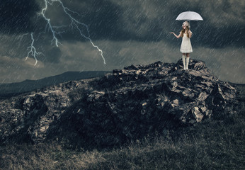 Girl with a white umbrella stands on the top of a mountain