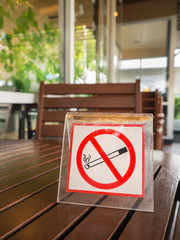 No smoking sign displayed on the wooden table in the public cafe