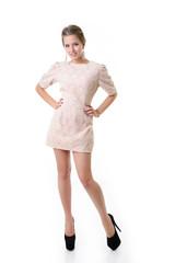 Attractive fashion girl dressed in elegant beige dress, full len