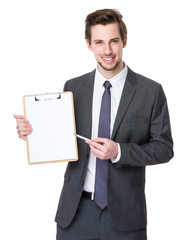 Happy smiling young business man showing blank clipboard