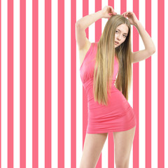 Young fashion woman posing over striped pink-white background.