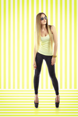 Young fashion woman posing over striped yellow-white background.