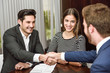 Smiling young couple shaking hands with an insurance agent - 81116709