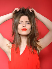 Attractive fashion girl makes faces posing at studio over red ba
