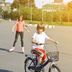 Little boy bike on bicycle and teen girl on roller skates behind