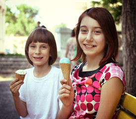 Children eating ice-cream in the summer park , toned.