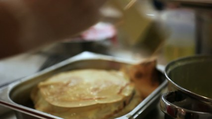 Female hands chef lubricates brush butter pile of tasty pancakes