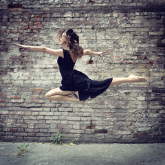 Attractive teen girl dancing outdoor against grunge bricks wall.