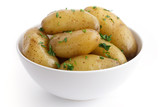 Shiny boiled small potatoes with parsley in bowl.