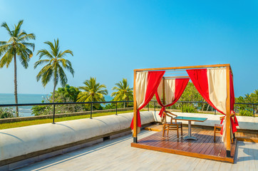 Pergola with tables and chairs, red curtains on luxury hotel