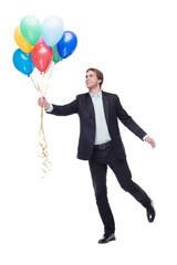 Smiling man holding a lot of colourful balloons