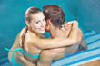 Smiling couple sitting in swimming pool