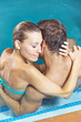 Happy couple embracing in hotel pool