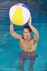 Man in swimming pool with water ball
