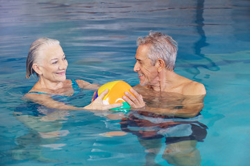 Happy senior couple playing water ball