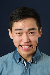 Laughing young Asian man looking at camera