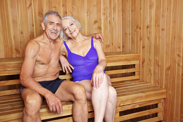 Happy senior couple together in sauna