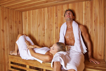 Couple sitting and laying in sauna