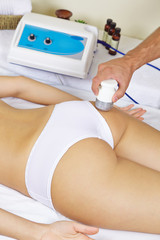 Woman getting electric massage at buttocks