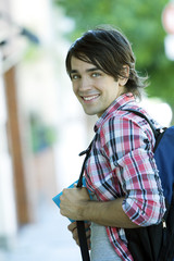 Happy young man with backpack and books, back to school